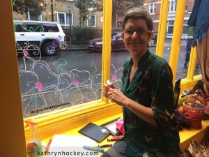 artist at work, kathryn hockey, artist, illustrator, bermondsey street, marys living and giving shop, window, design, springtime, birds, swallows, bees, flowers, here comes the sun, illustration, glass, chalk, pens, drawing, design, london